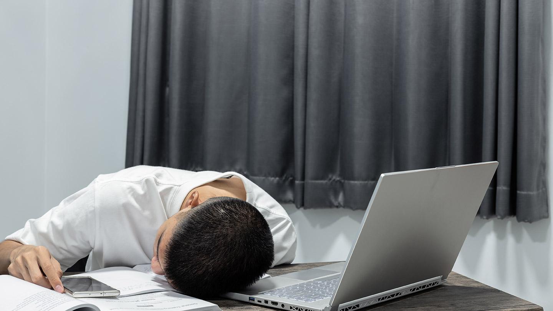 パソコンの前で勉強に疲れる学生